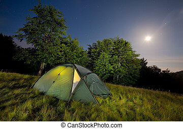 Night view with the tent, moon and the stars