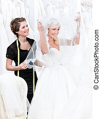 Shop assistant helps to the bride to put the wedding gown...