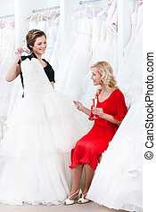 Shop assistant proposes another dress to the bride