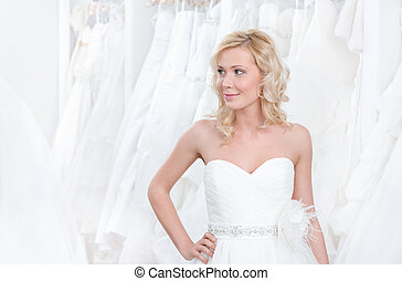 Trying a beautiful wedding gown on - Youg girl is trying a...