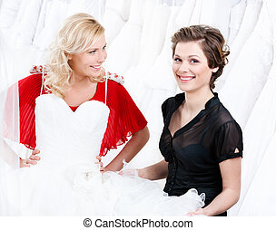 Hesitating about the wedding gown.Shop assistant persuades...