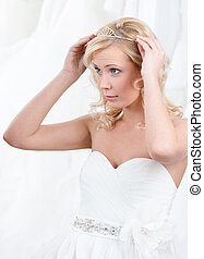 Charming bride puts tiara on her head, white background