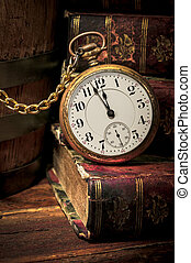 Old pocket watch and books in Low-key
