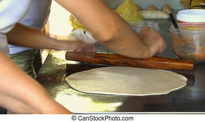 Female cook rolling dough with rolling-pin.
