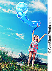 flying bubble - Happy girl is playing with big bubbles in a...