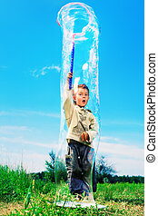childhood - Cute little boy is playing with big bubbles...