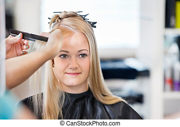 Woman Getting Hair Combed - Mirror reflection of young woman...