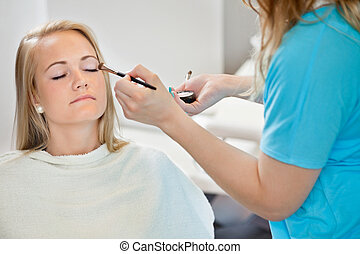 Beautician Applying Make Up To Woman - Midsection of...