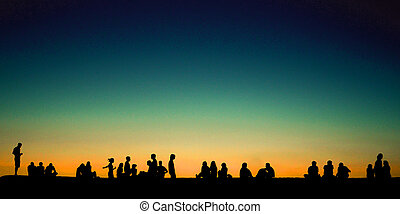 Group of young people sitting on wall at sunset
