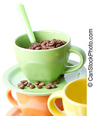 The green cup with a spoon full of coffee beans on a light...