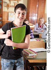 Smiling boy in front of class - Smiling schoolboy with...