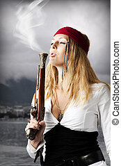 Girl pirate blows a smoke from a old pistol - Girl pirate...
