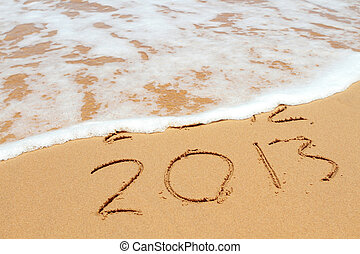 2013 year on the sand beach near the ocean. 2012 is been erasing by wave