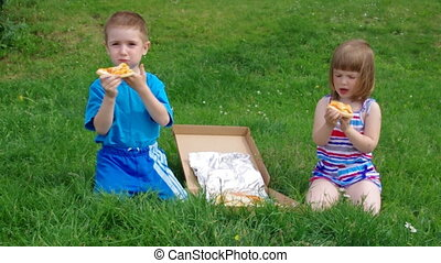 Picnic on the grass. boy and small girl have a dinner with...