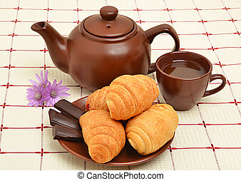 Brown teapot, cup and sauser with croissant and chocolate