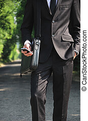 Business man with phone on road