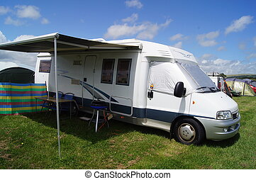 Motor Home - Motor home with its awning open camped in a...