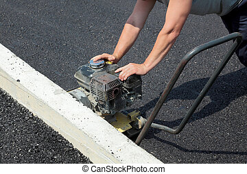Roadworks - Worker with compactor at a road construction...