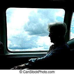 SENIOR WOMAN ON AIRPLANE - A senior woman in silhouette sits...