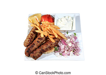 shish kebab served with fried potatoes and sauce on a plate...