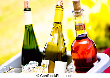 three wine bottles in green, red and yellow outdoors