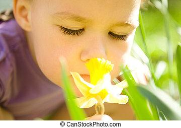 Portrait of a cute little girl smelling flower