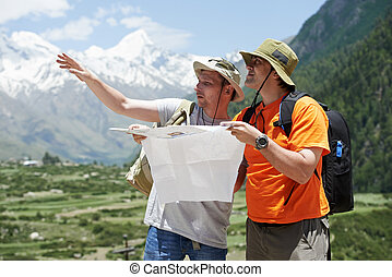 Tourist travellers with map in mountains