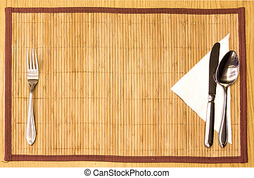 Table appointments- fork,knife,spoon, silk napkin on bamboo...