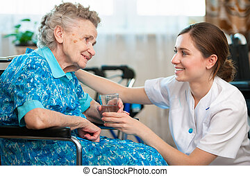 Home care - Senior woman with her caregiver at home