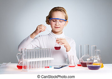 Clever girl - Little girl playing scientist pipetting fluid...
