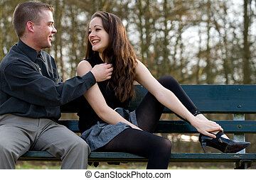 Young couple having fun - Man and girlfriend on a bench in a...