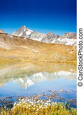 Grossglockner in Austria mirrored on alpine pond - Snowy...