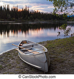 Sunset sky and canoe at Teslin River Yukon Canada - Canoe...