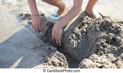 Children play with sand ashore sea