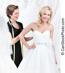 Seamstress adjusts the dress of the bride, white background