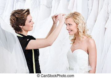 Shop assistant helps to fix the wedding tiara, white...