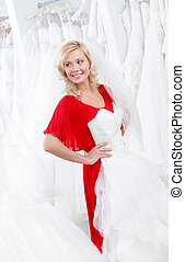 Putting a wedding gown on - Young girl puts a wedding gown...