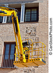 Hydraulic platform equipment against building wall Vertical...