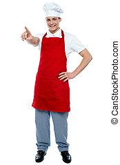 Male chef in uniform pointing away and smiling