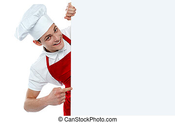Male chef indicating at blank menu isolated over white...