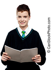 Charming schoolboy holding workbook and looking at camera