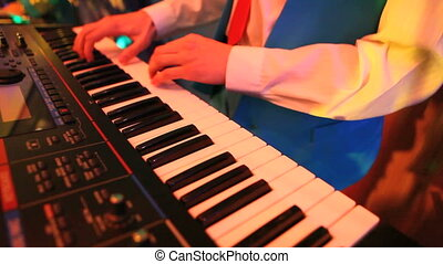Playing on the piano - Male hands playing on piano at event...