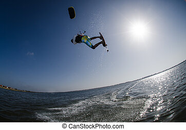 Kite Surfer - Kiteboarder flying over the water on a sunny...