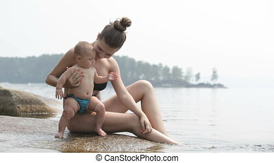Childcare - Pretty mother and baby on the beach at...