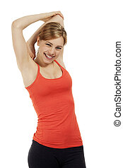 young happy fitness woman in red shirt stretching her arms on white background