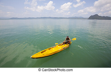 Young Man Rowing A Canoe