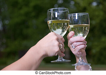 Wine Toast Glasses and Chardonnay Outdoors - Two female...