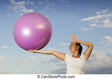 Cute woman working out with a ball