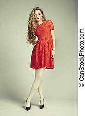Fashion photo of young magnificent woman in red dress Studio...