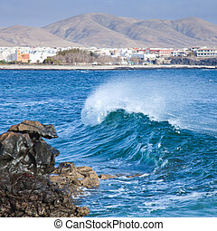 breaking wave, El Cotillo in the background